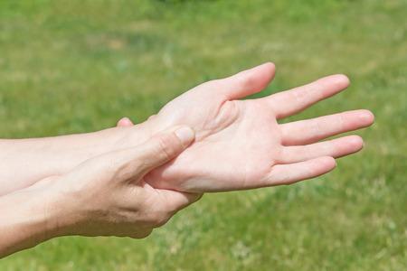 야외에서 손목 관절 증후군 문제를 보여주는 여성 손