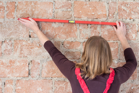 overall: Redhead young woman dressed in red overall is using a spirit level on an old brick wall. Woman is turned back to the camera.
