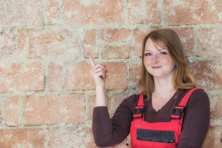 half dressed: Attractive young redhead woman dressed in red overall is standing  in front of an old brick wall. Woman is looking at the camera and is pointing the finger at the wall.  Place for your text is in the left half of the image.