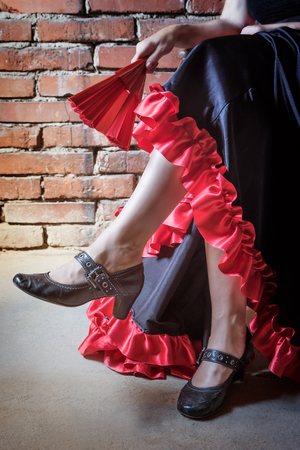 deliberately: Close up view of leg of woman sitting on a chair and dressed in costume of Flamenco dancer with an closed red and black fan. The photo has deliberately darkened edges. Vertically.