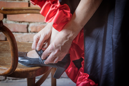 deliberately: Closeup view of a Flamenco dancer with her foot on an old wooden chair and putting on the black old shoe. The photo has deliberately darkened edges