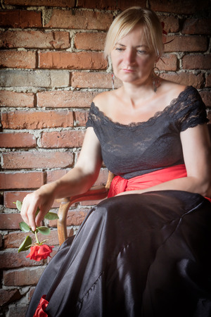 deliberately: Middle aged woman dressed in costume of Flamenco dancer is sitting on a old wooden chair. Old brick wall is in the background. The photo has deliberately darkened edges. The woman has lowered eyes