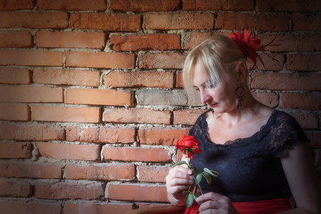 deliberately: Middle aged woman dressed in costume of Flamenco dancer is holding a red rose in her hand. Old brick wall is in the background. The photo has deliberately darkened edges. Stock Photo