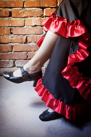 deliberately: Close up view of legs of woman sitting on a chair and dressed in costume of Flamenco dancer. The photo has deliberately darkened edges. Vertically.