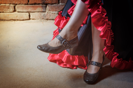 deliberately: Close up view of legs of woman sitting on a chair and dressed in costume of Flamenco dancer. The photo has deliberately darkened edges. Horizontally.