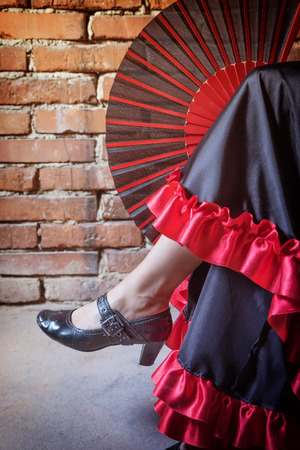 deliberately: Close up view of leg of woman sitting on a chair and dressed in costume of Flamenco dancer with an open red and black fan. The photo has deliberately darkened edges. Vertically.