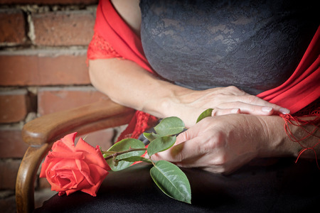 deliberately: Closeup view of the hands of middle aged woman dressed in costume of Flamenco dancer sitting on a chair and holding a red rose in her lap.The photo has deliberately darkened edges. Stock Photo