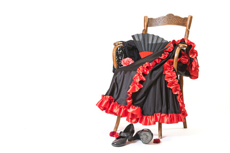 Clothing and shoes for Flamenco dance are lying on a vintage wooden chair. All is on the white background.