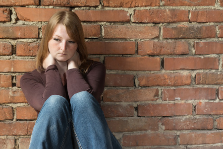 Sad redhead young woman is sitting in natural light in front of an old brick wall. Stock Photo
