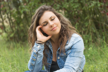 Portrait of dreaming teenage girl sitting outdoors. Girl has closed eyes.