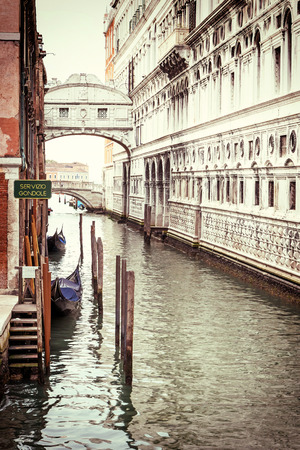 edited photo: Photo of the Bridge of Sighs (Ponte dei Sospiri ) with gondolas dock in Venice (Italy). Photo is edited as a vintage with dark edges. Stock Photo
