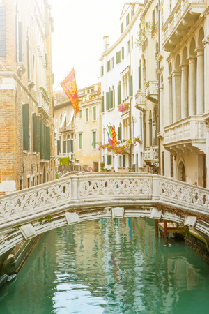 edited photo: The peaceful Venetian canal with a bridge. Edited with a sun lights on top of the photo.