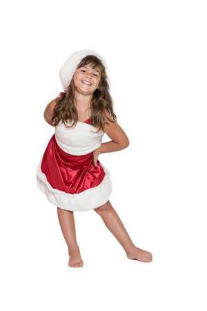 leaning forward: Cute brunette little girl in Santa Claus costume is leaning forward in front of the camera isolated on the white background. Stock Photo