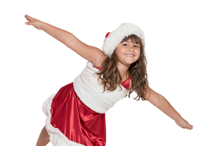 leaning forward: Cute smiling little girl in Santa Claus costume is leaning forward in front of the camera with her arms outstretched. All is isolated on the white background.