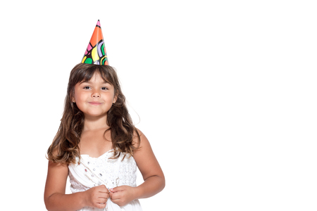facing right: Cute tanned little girl in white dress with paper hat on her head is standing facing the camera isolated on the white background looking at the camera. Free place for yout text is in the right side of the photo.