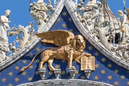 Closeup view of winged golden lion statue on the roof of the Cathedral of San Marco (Venice, Italy). Vertically.