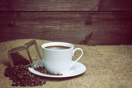 edited photo: White cup of coffee standing on the sackcloth. Around it are scattered coffee beans and ground coffee glass  Wooden desk on the background fills a half of the photo. Edited as a vintage photo.