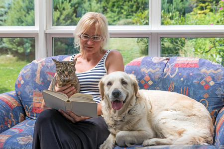 Blond middle aged woman is sitting on a couch and reading a book. Striped cat and Golden Retriever dog are sitting with her together. The pets are looking at the camera.  Banque d'images