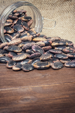 edited photo: Beans spilled from the lying glass on burlap sack and wooden desk. Edited as a vintage photo with dark edges. Vertically. Stock Photo