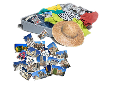 Studio shot of a suitcase with scattered clothing and straw hat. Photos of Bruges landmarks are lying in front of the suitcase. Everything is on a white background. Stock Photo