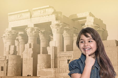 edited photo: Smiling long haired tanned little girl with her finger over her mouth is standing in front of Kom Ombo temple in Egypt. Landmark in the background is edited as a  vintage photo in sunlight. Stock Photo