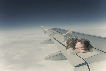 edited photo: Smiling little girl is lying on the wing of an aircraft in flight. Edited as a vintage photo.