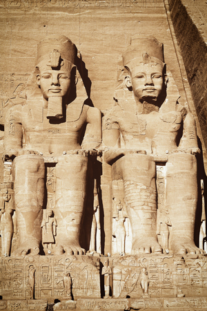 edited photo: The Abu Simbel temple. View of the statues represent Ramesses II and his wife Nefertari. Edited as a vintage photo with dark edges.