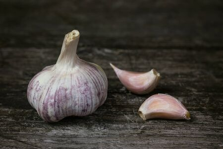 edited photo: Bulb of garlic and two garlic cloves on an old wooden table. Edited as a vintage photo.