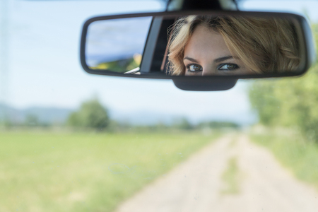 The beautiful eyes of the young driver woman are reflected in the rearview mirror. Blurred road and landscape is in the background. 版權商用圖片