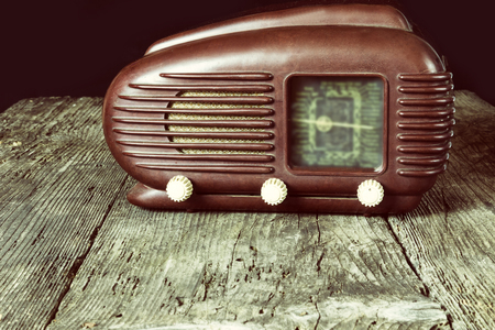 removed: Vintage photo of old radio standing on the old wooden desk. Released in 1953. All potential trademarks are removed and blurred.