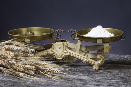Vintage kitchen scales with scoop of flour are standing on the old wooden desk. The bundle of corn lies in the foreground. Stock Photo