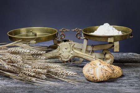 小麦粉のスクープとビンテージのキッチン スケールは古い木製机の上に立っています。トウモロコシとペストリーのバンドルは、前景にあります。 写真素材