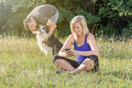 La mujer rubia joven está usando su teléfono inteligente mientras su pareja está jugando con los perros en el fondo . Foto de archivo - 85536186