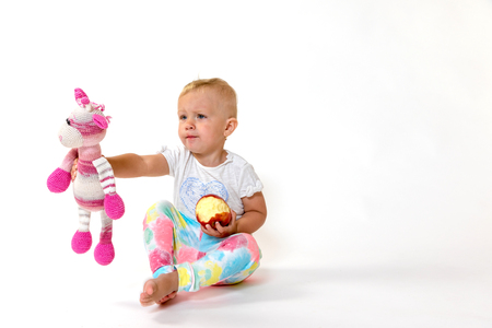 Studio shot of toddler girl holding red apple and fabric toy. All is on the white backgropund. Horizontally.