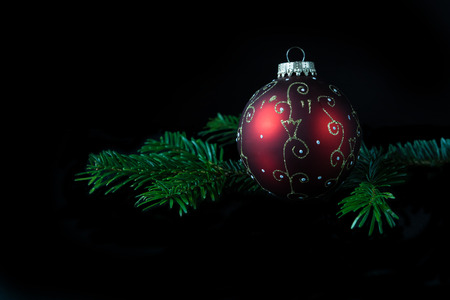 Low key view of Christmas bulb and a twig of Chritmas tree.  Stock Photo