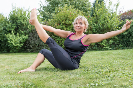 Attractive senior blond woman in single straight leg stretch pose with outstretched arms in the garden. Woman is looking at the camera.