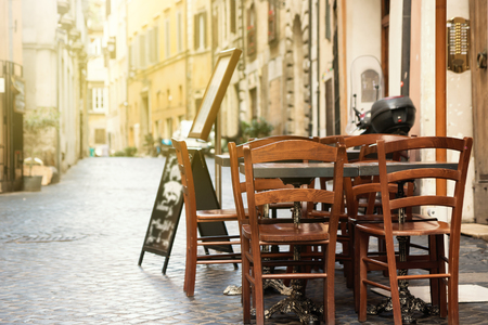 Empty dining table with chairs is standing in a empty street lit by morning sunlight. Rome, Italy. All potential trademarks are removed or blurred.