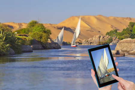 Hands of tourist touching tablet screen with a focused sailboat sailing on the Nile. Intentionally blurred image is in the background. Nile near egyptian city Aswan. Egypt.
