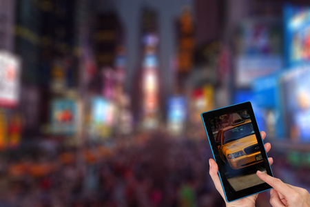 Finger touching tablet with a yellow taxi cab in the screen. Intentionally blurred night image of a Times Square in the New York City is in the background. All potential trademarks are removed.