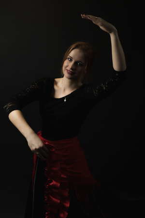 Portrait of posing young woman dancing flamenco. All on the dark background.