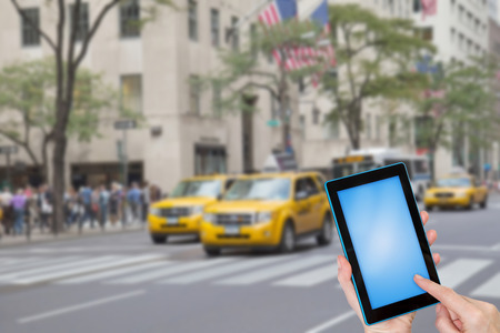 Female finger touching tablet blue blank touchscreen ready for your text. Intentionally blurred image of a Fifth Avenue (NYC) is in the background. All potential trademarks are removed. Фото со стока