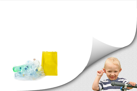 Smiling blond boy is looking at a camera. Pile of plastic waste is lying on the white background. The empty yellow bag is standing next to them. All potential trademarks are removed.