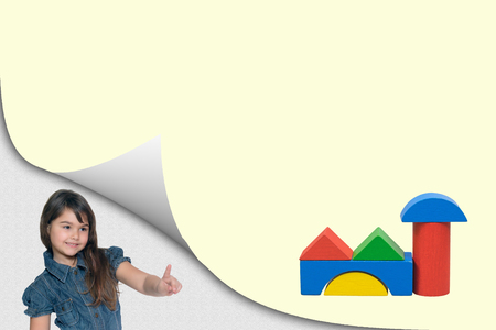 Building concept. Cute tanned little girl is showing at a blank yellow page with curl effect with a building toy created from colorful wooden cubes ready for your text. Imagens