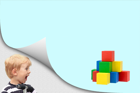 Surprised blond boy standing in an exposed corner is looking at blank page with a pyramid created from colorful wooden cubes.