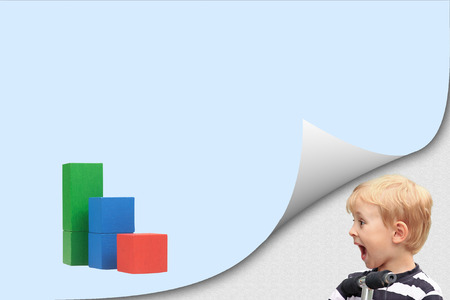 Surprised blond boy standing in an exposed corner is looking at blank page with a graph created from colorful wooden cubes.