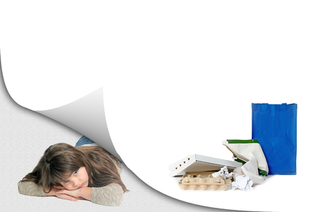 Blank page with curl effect and sad little girl lying in an exposed corner looking at the camera. Blank page with a pile of paper waste with ready blue bag is ready for your text.  All potential trademarks are removed.