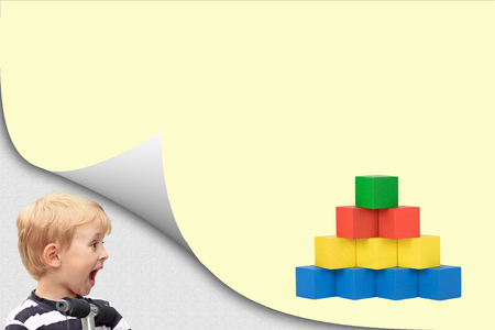 Surprised blond boy in an exposed corner is looking at blank yellow page with a pyramid created from colorful wooden cubes.