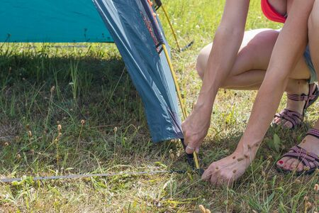 Closeup view of woman building outdoor tent. All potential trademarks are removed.