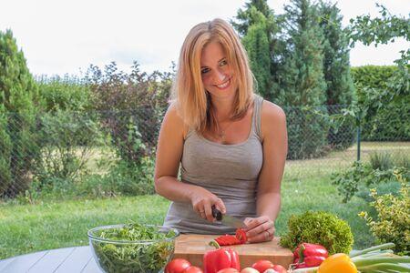 La giovane donna attraente sorridente sta affettando i pomodori all'aperto.