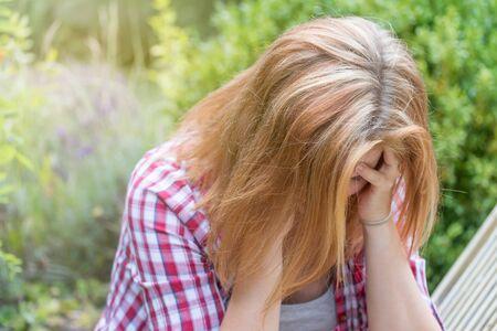 Attraente giovane donna dai capelli lunghi che tiene le mani sopra la testa e guarda in basso. È depressa.